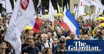 Dutch protesters march through The Hague against 'corona pass' - The Guardian