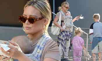 Hilary Duff is every inch the hands-on mom as she carries five-month-old Mae in a sling
