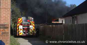 Huge plumes of smoke and large flames as fire grips building containing 'large amount of rubbish'