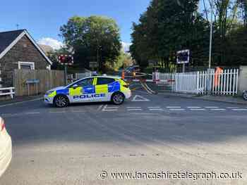 Car hits level-crossing barrier closing road in both directions