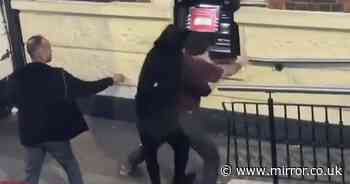 Two men scrap at cash machine as onlookers just stand by and film it on their phones
